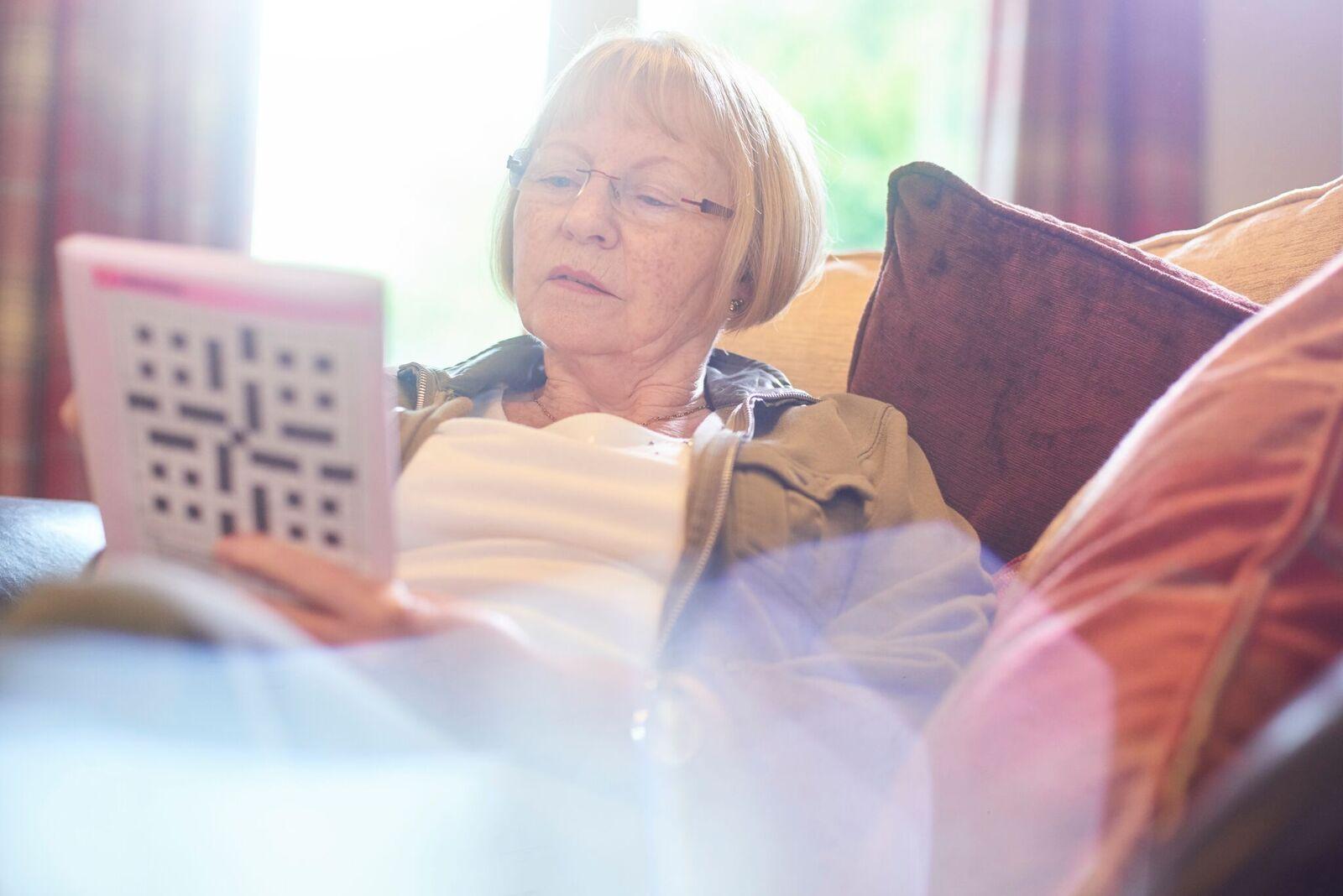 femme âgée faisant des mots croisés