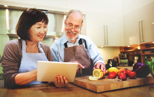 senior couple reading recipe from tablet