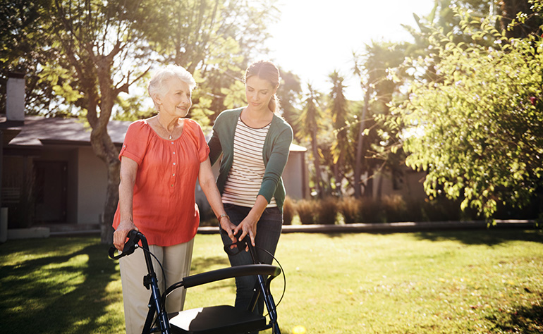 young woman helping senior woman with walker