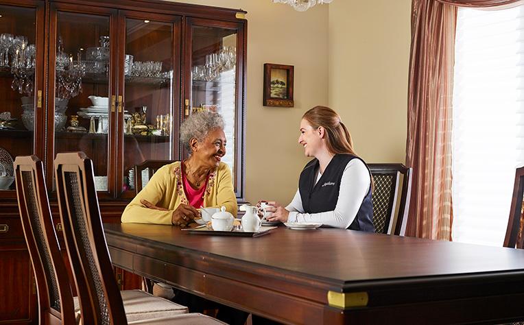 soignant prenant le thé avec une femme âgée