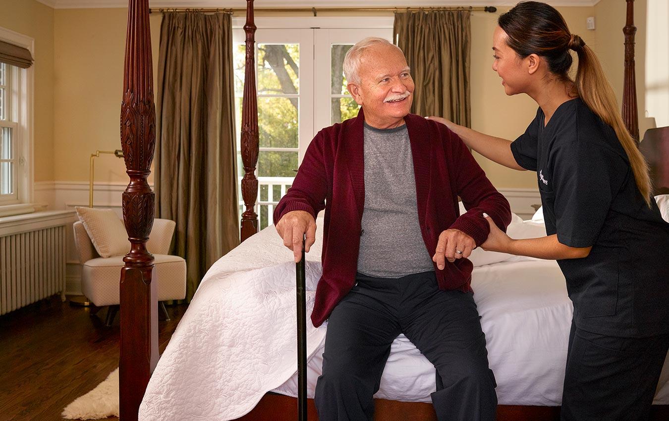soignant aidant un homme âgé à sortir du lit