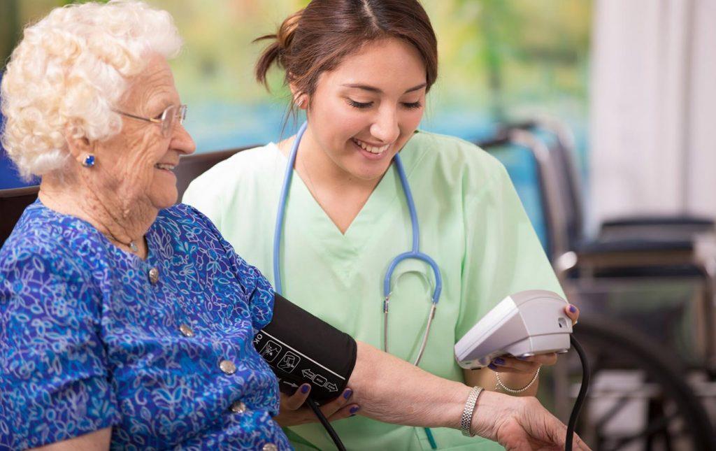 infirmière prenant la tension artérielle d'une femme âgée
