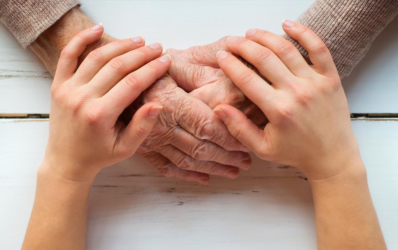 mains âgées et mains d'enfant embrassant