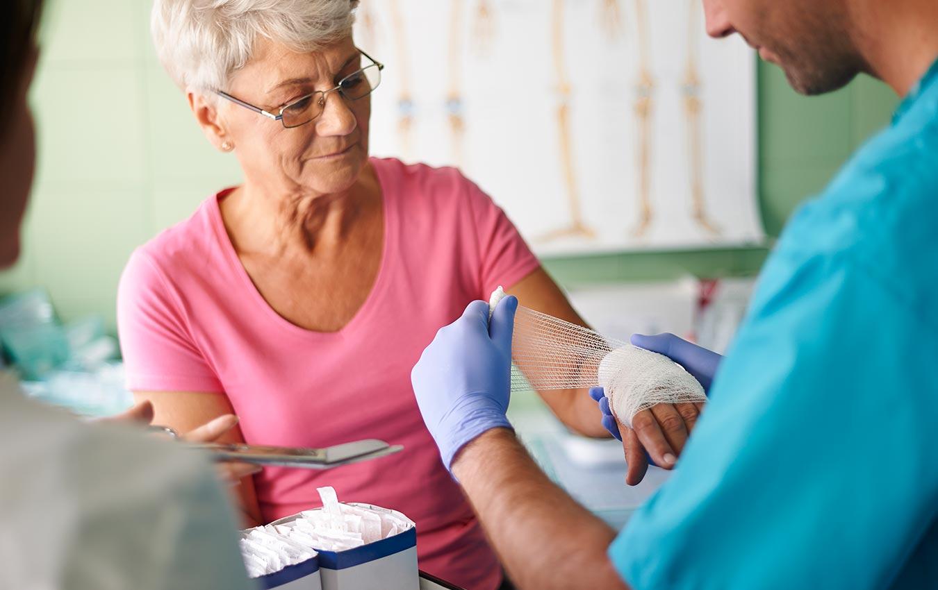 infirmière mettant un bandage sur une femme âgée