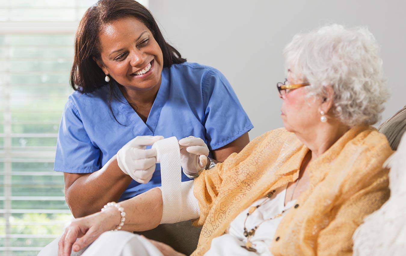 soignant mettant un bandage sur une femme âgée