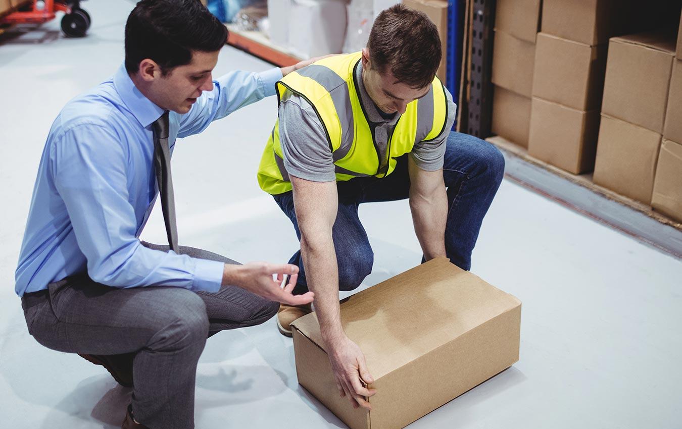 homme aidant un autre homme à soulever une lourde boîte