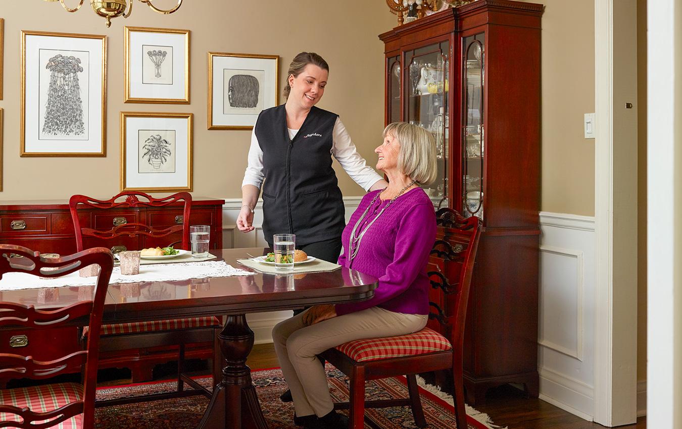 soignant au dîner avec une femme âgée