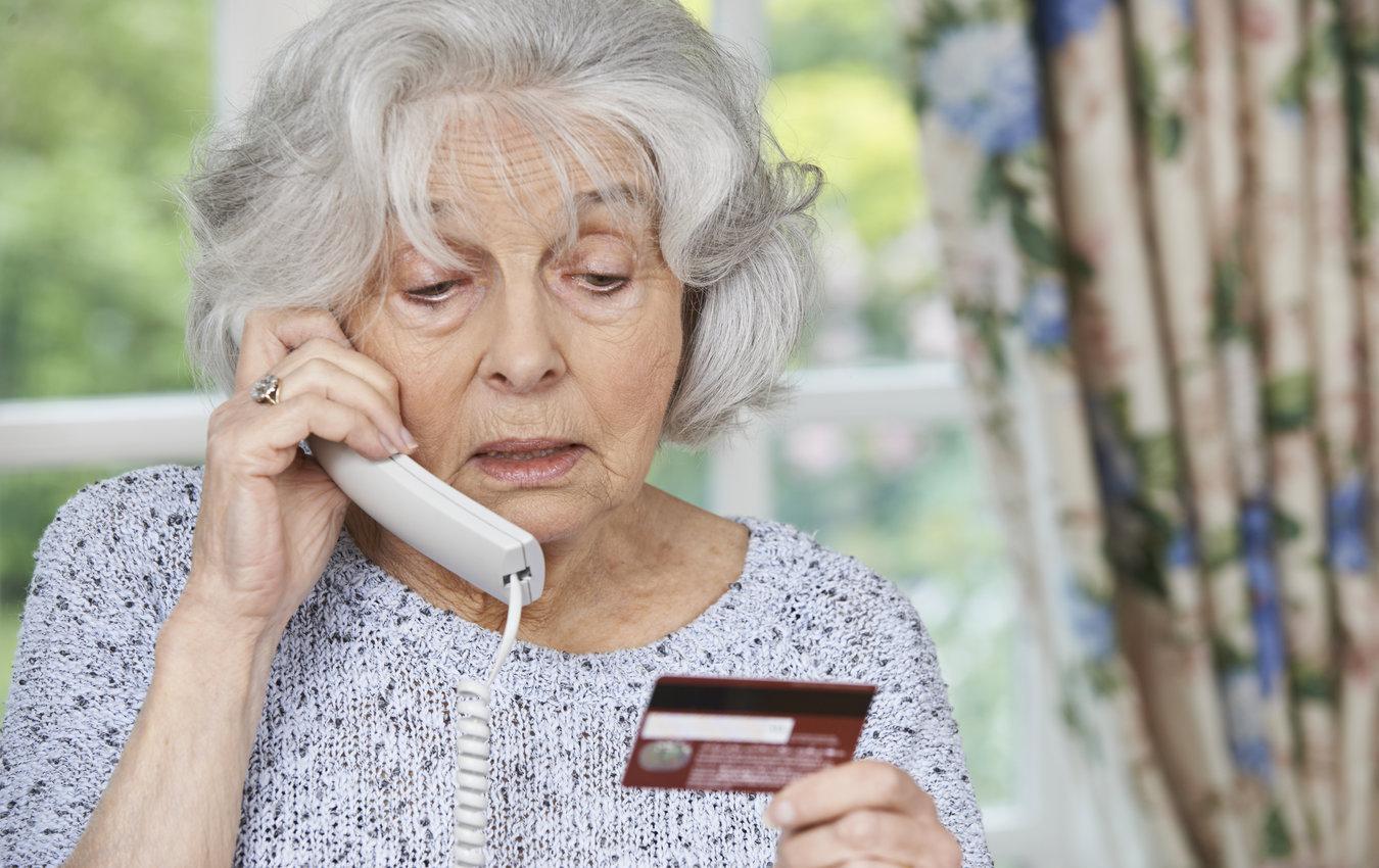 femme âgée au téléphone tenant une carte de crédit