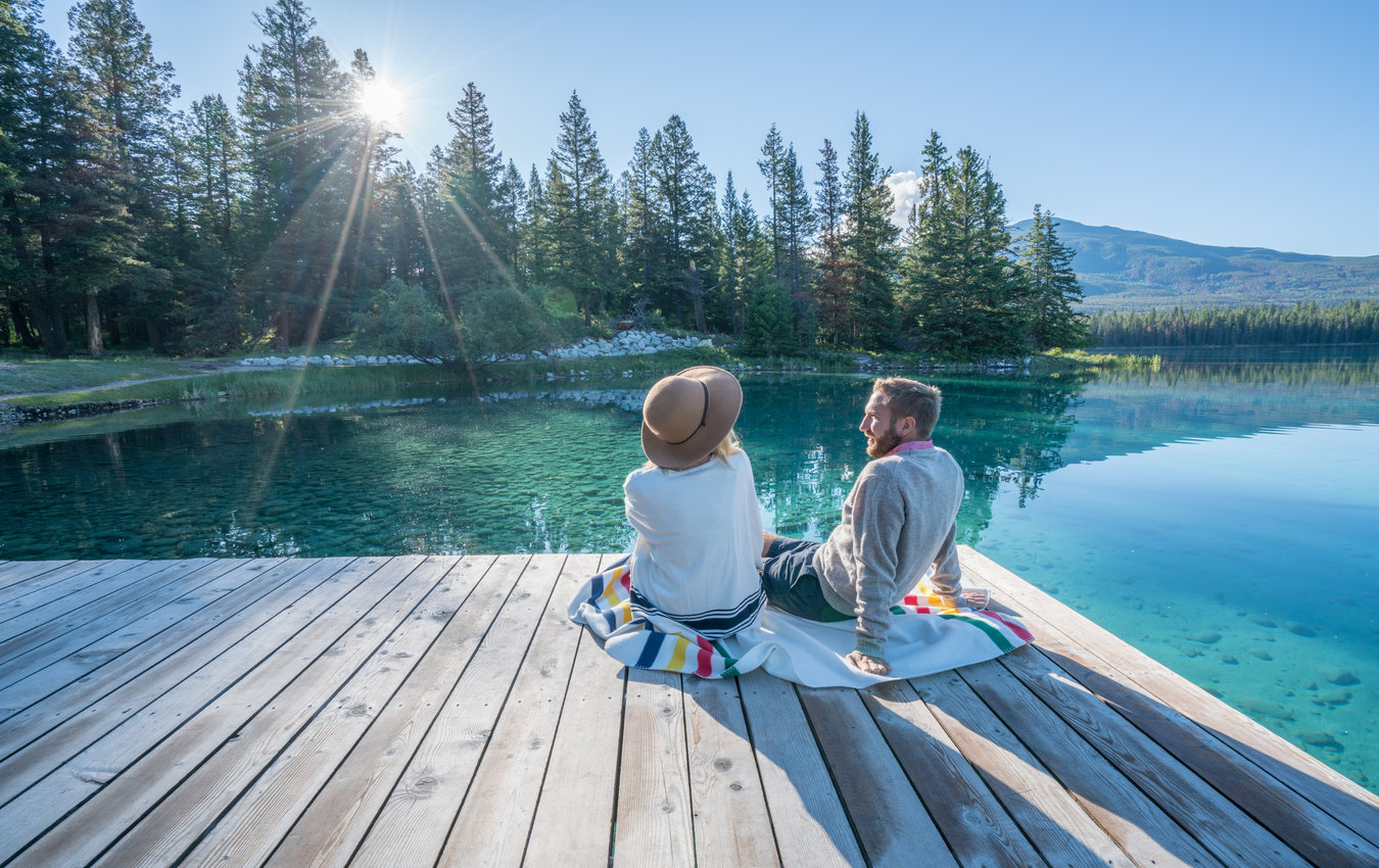 couple assis sur le quai en face des montagnes