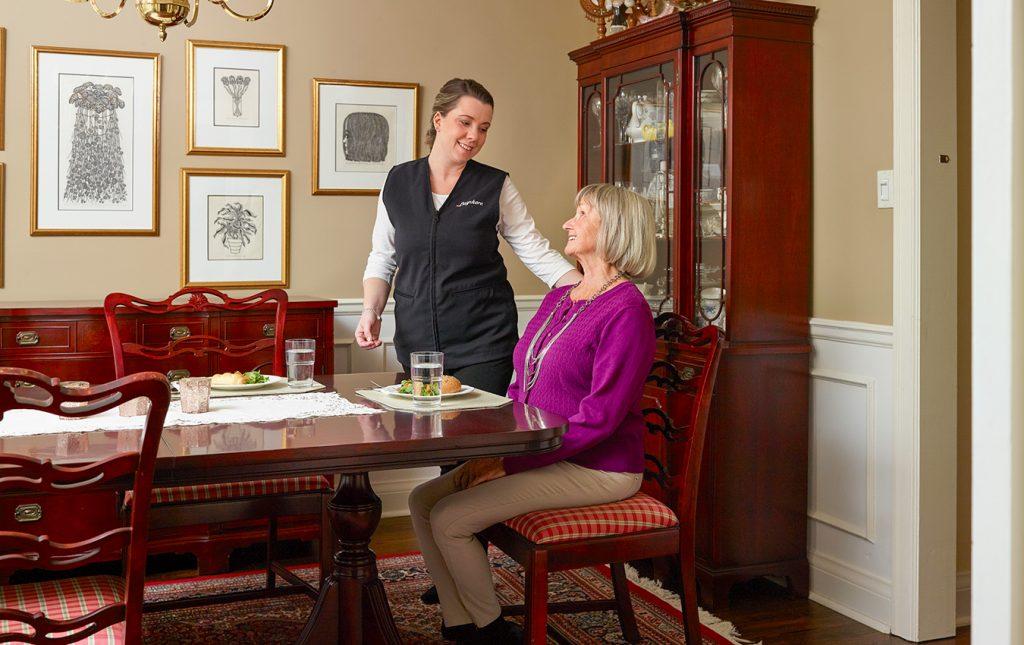 soignant et femme âgée au dîner