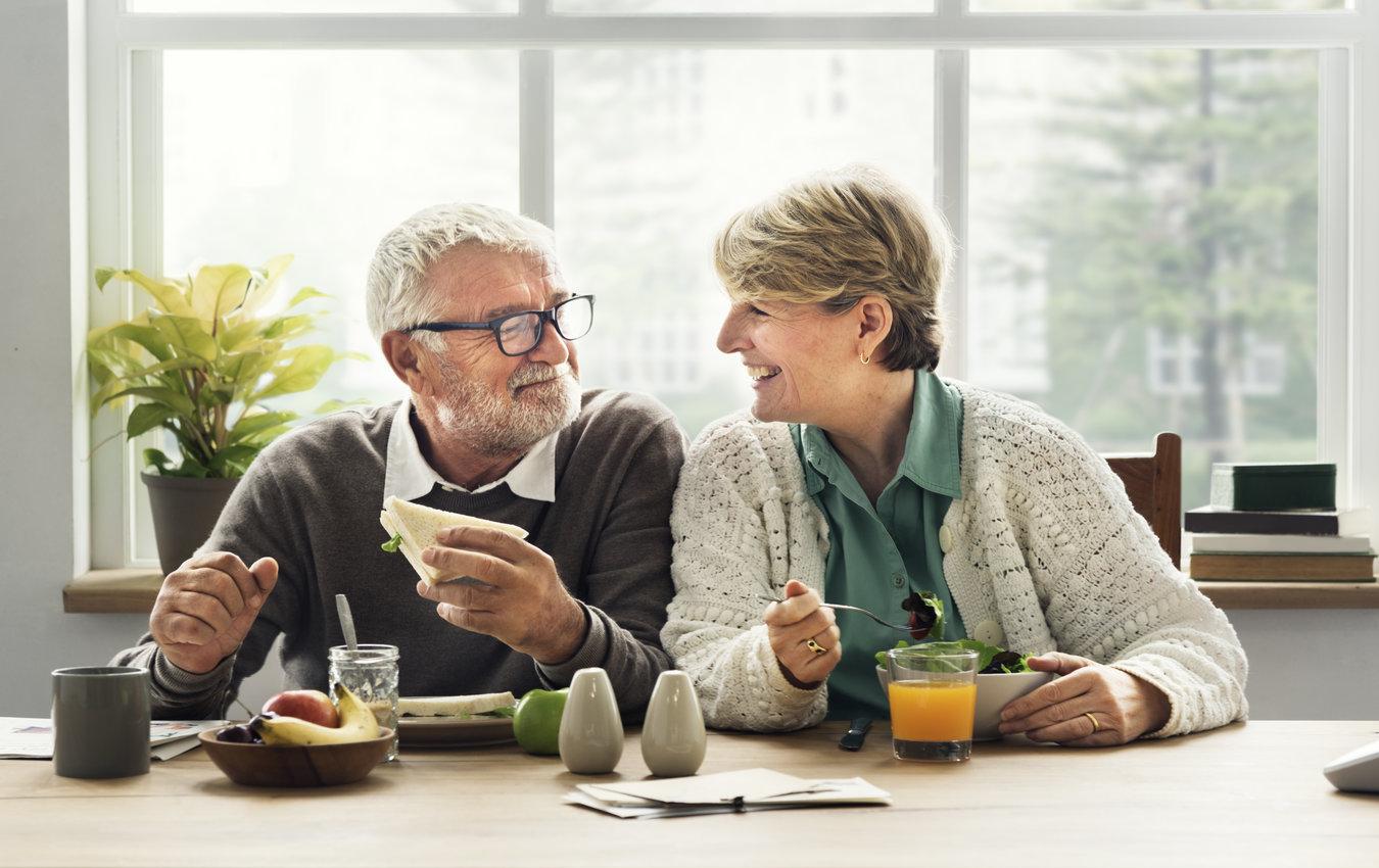 couple de personnes âgées en train de déjeuner, souriant