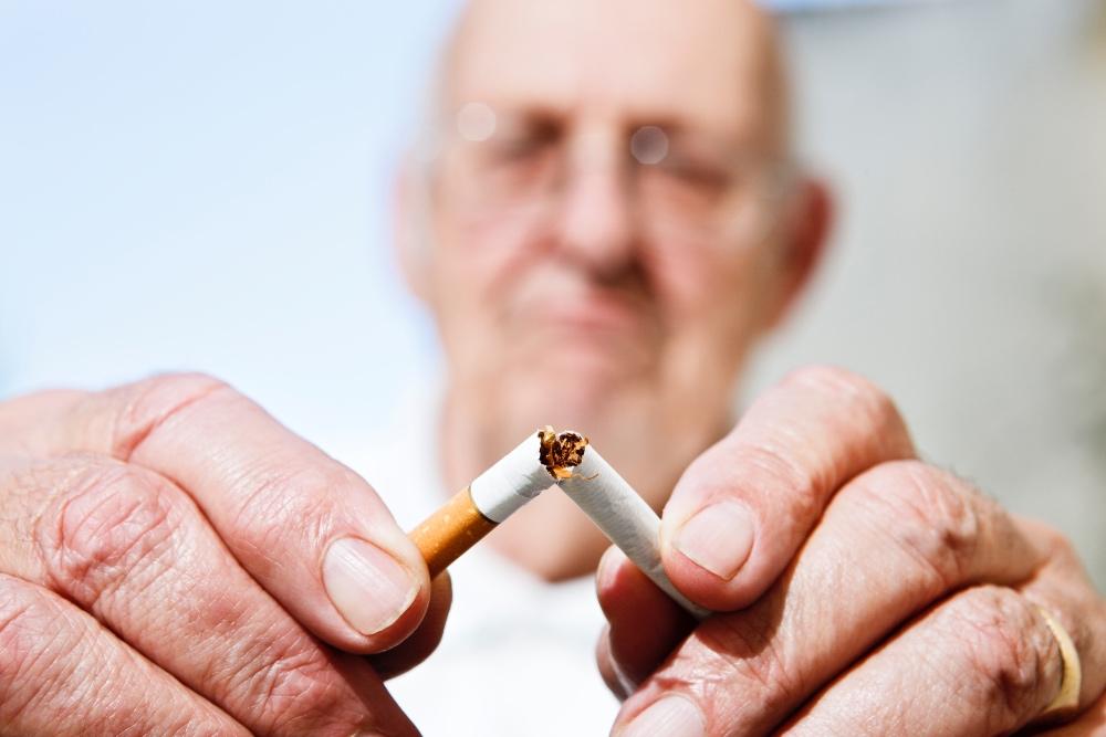 senior man snapping cigarette in half