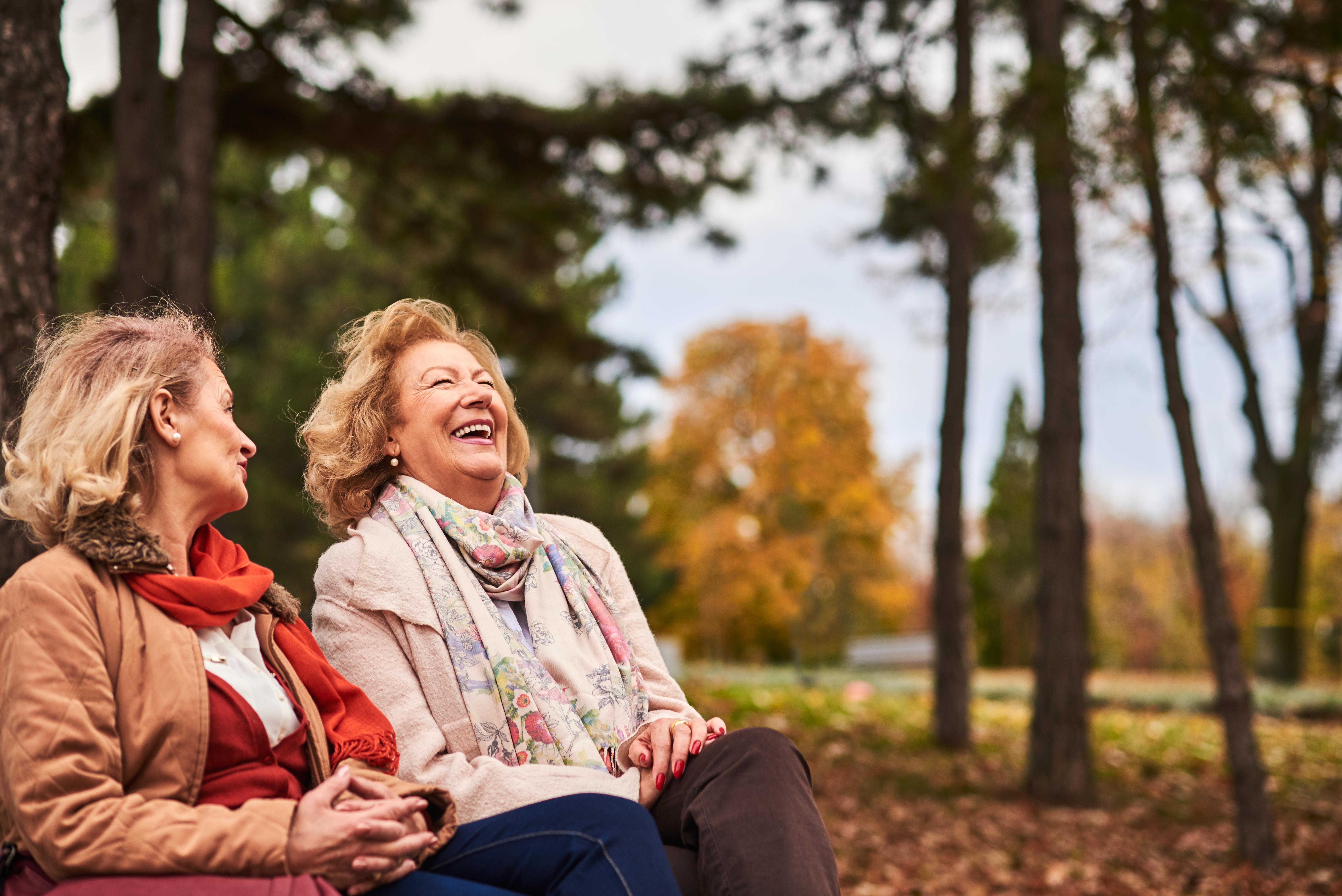 two senior women laughing in park