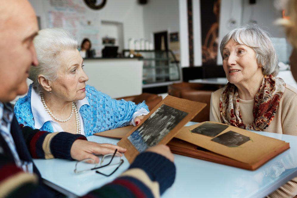 Aînés amicaux parlant tout en regardant à travers des photographies dans un café