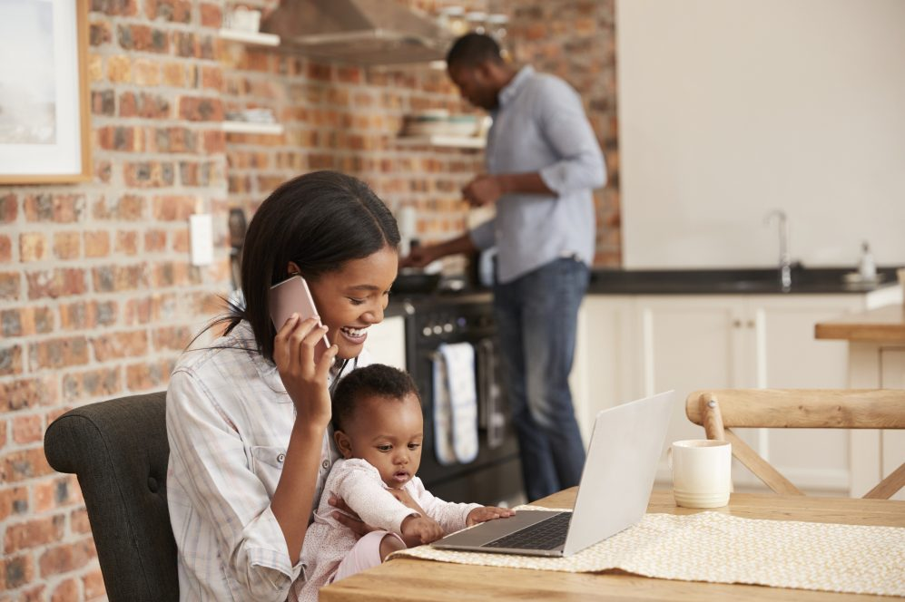 mère et bébé sur ordinateur portable dans la cuisine pendant que le père prépare le dîner