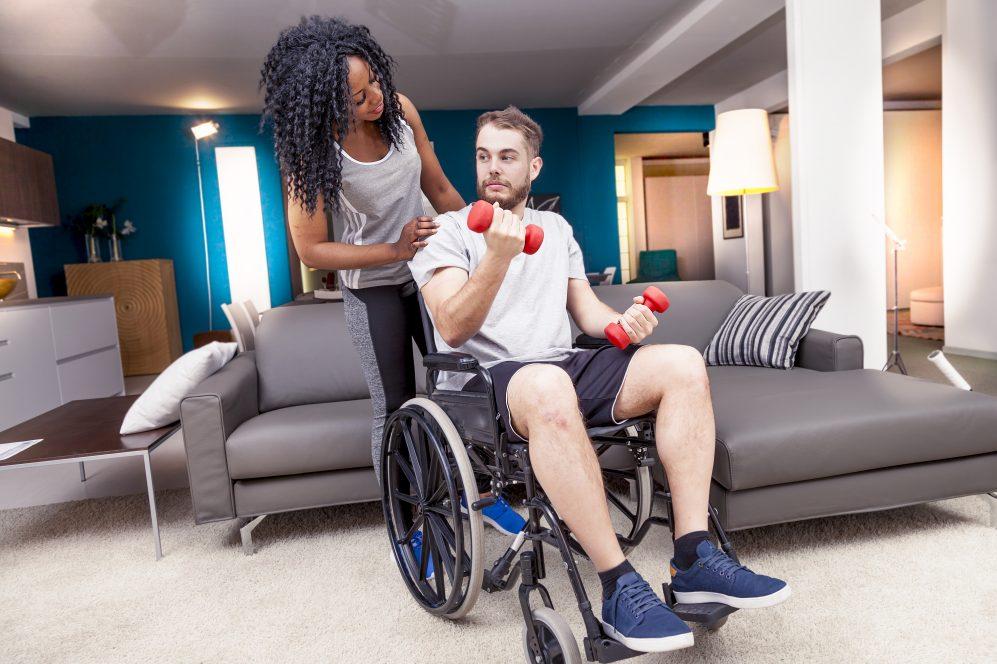 femme aidant l'homme en fauteuil roulant soulever des poids