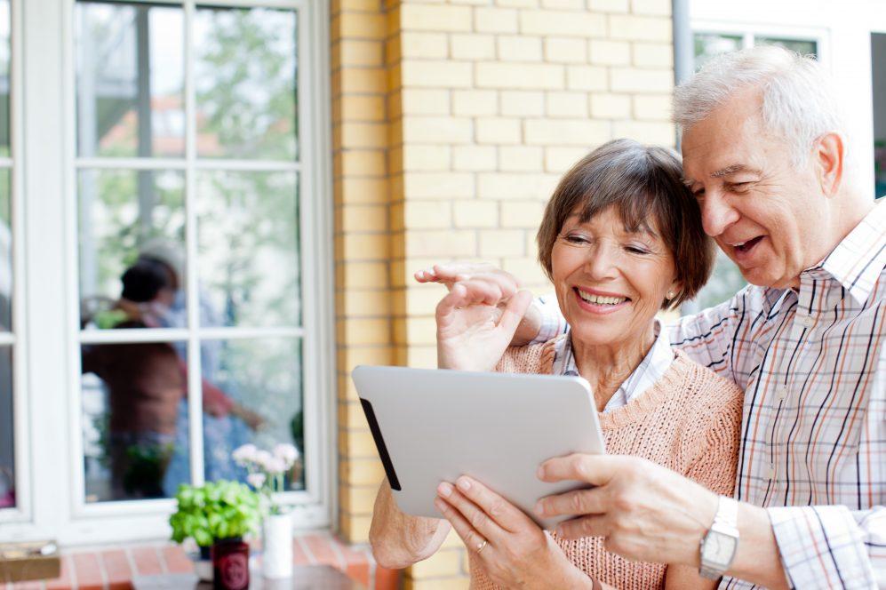 couple de personnes âgées souriant à la tablette