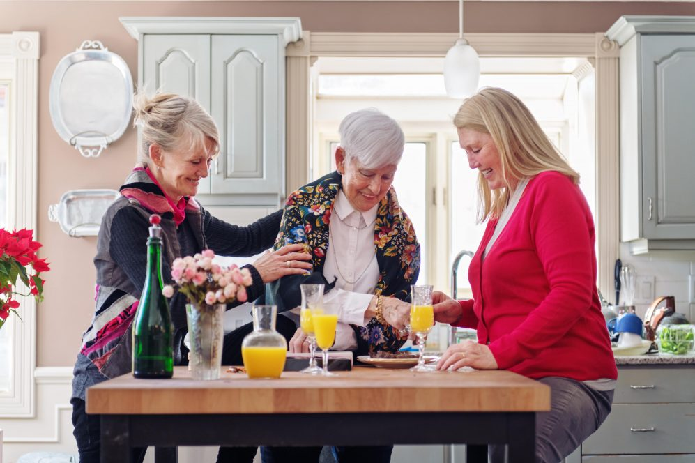 senior mother and daughters having drinks