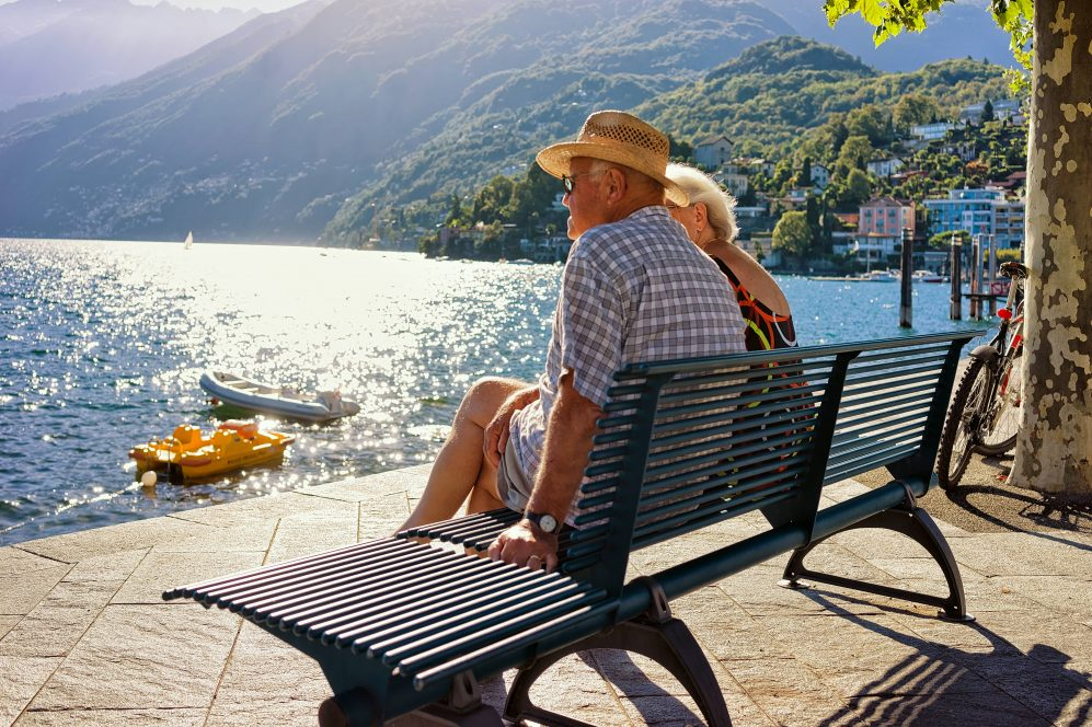 senior couple sitting on bench in vacation destination