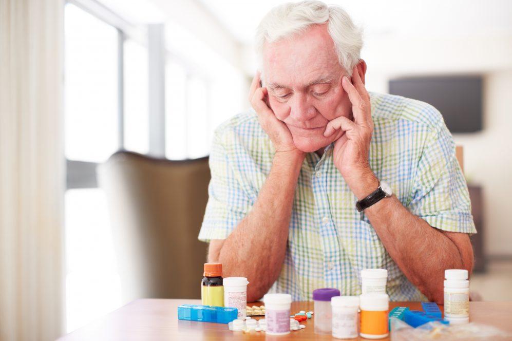 senior man looking at lots of medication