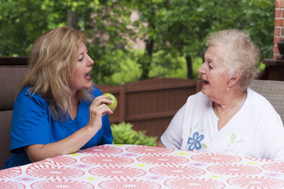 speech therapist teaching senior woman patient