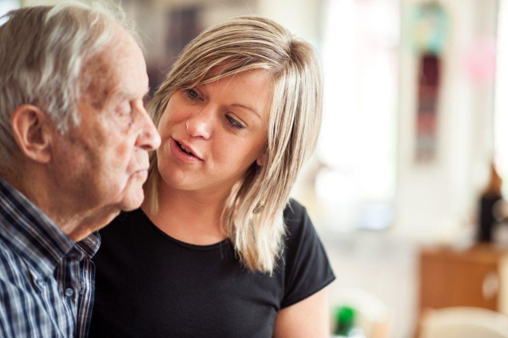 young woman talking to senior man