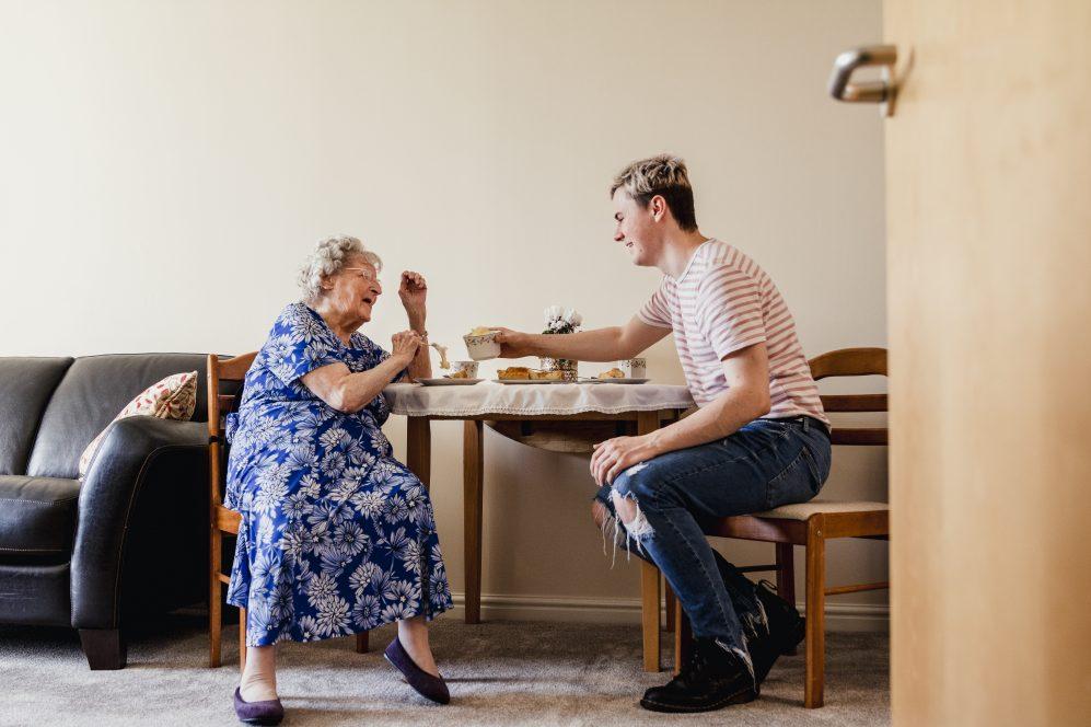 Jeune homme prenant le thé avec une femme âgée