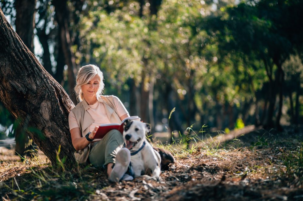 woman sitting in park reading with dog