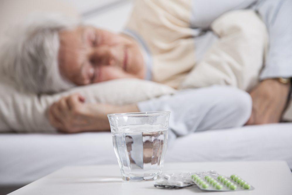 femme dormant dans son lit à côté de la table de chevet avec des pilules et de l'eau