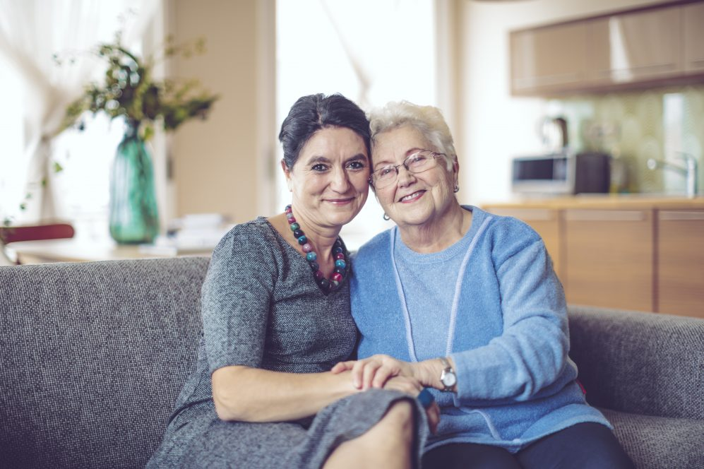 mère âgée et fille embrassant sur la table