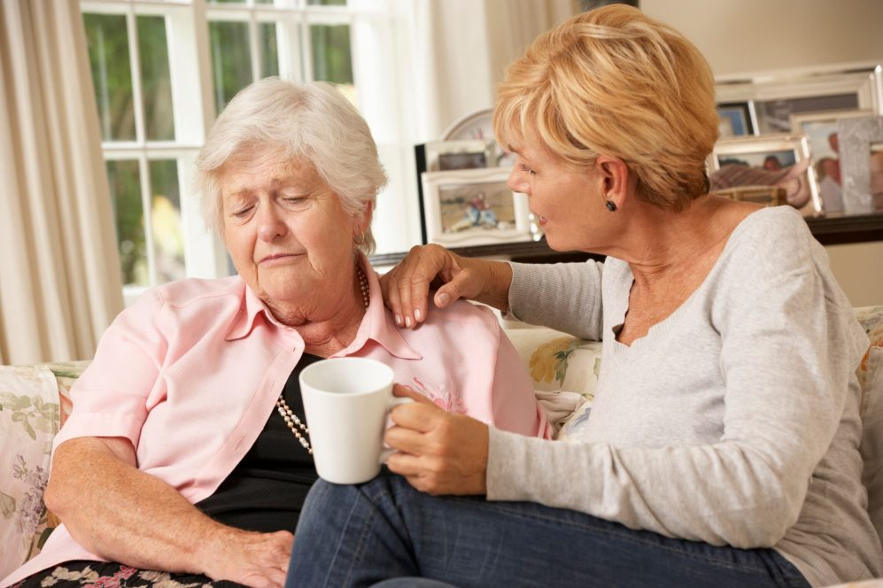 fille réconfortant mère âgée sur canapé