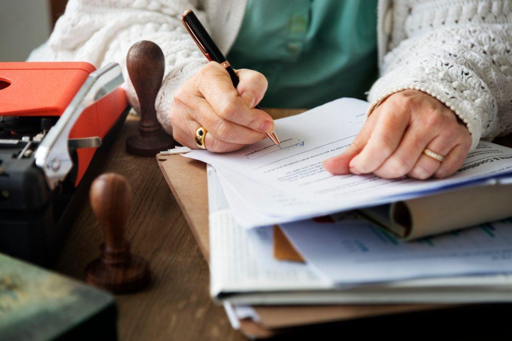 senior woman signing document