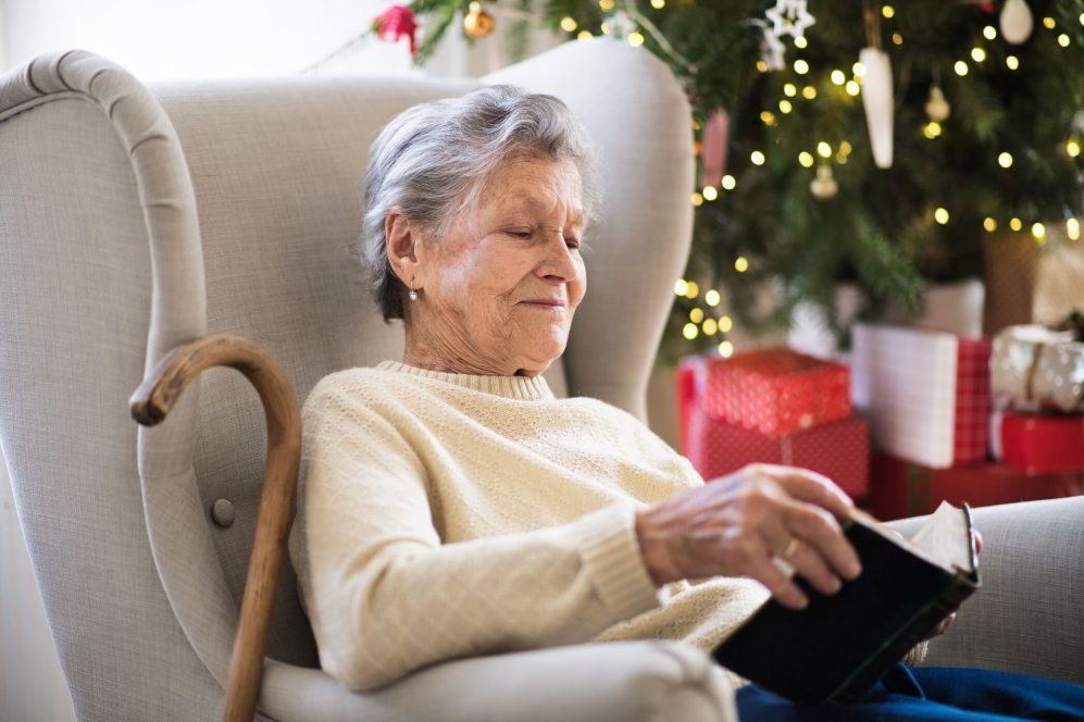 senior woman sitting on couch with cane reading book