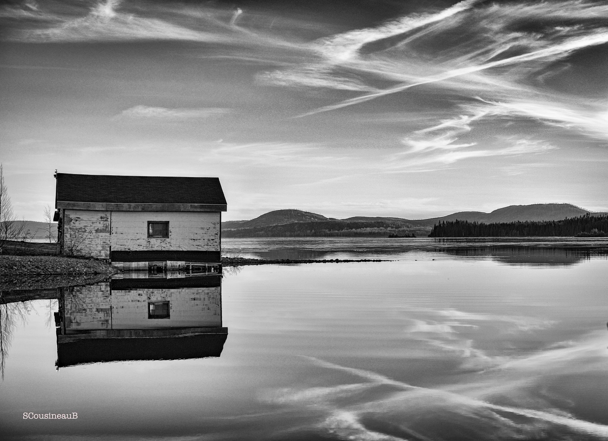black and white photo of solitary house on peaceful lake