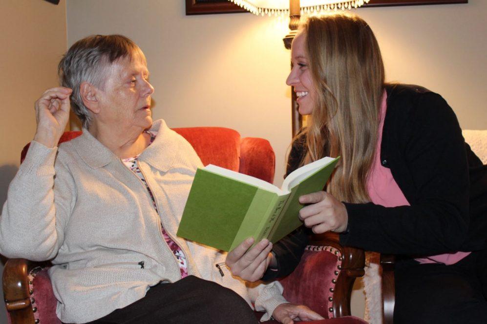 fille lisant avec une mère âgée