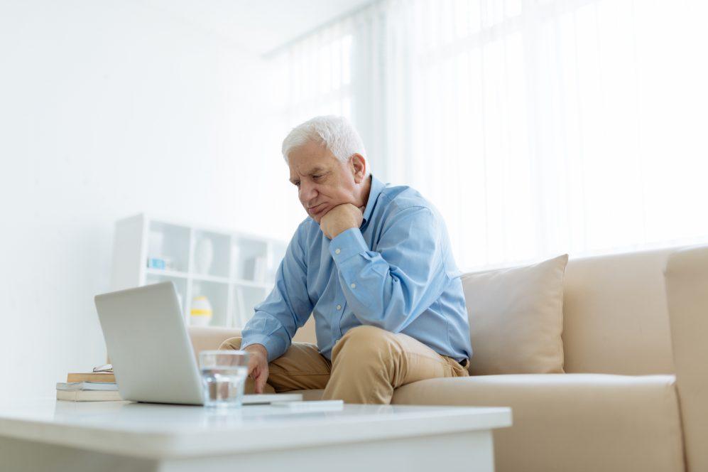 homme lisant un ordinateur portable sur un canapé