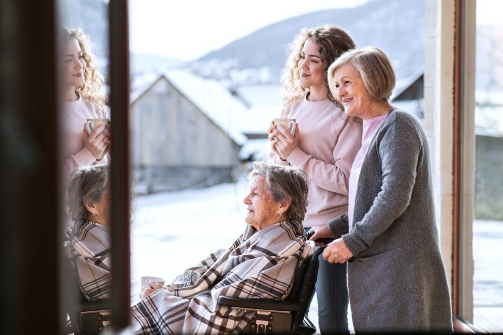 Grandmother, mother and daughter sitting on porch smiling