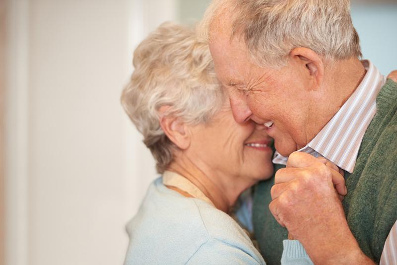 couple de personnes âgées souriant et embrassant