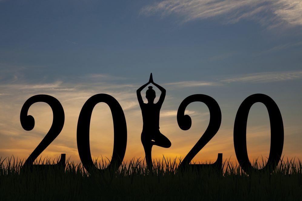 """femme faisant du yoga avec """"2020"""" en gros caractères"""