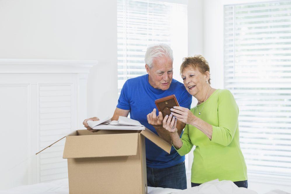 senior couple packing cardboard box and looking at photographs