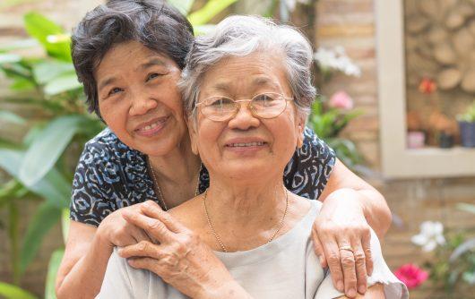Two female senior friends embracing