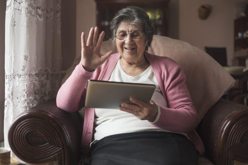 femme âgée à la maison à l'aide d'iPad