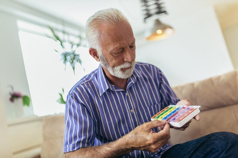 homme aîné prenant des pilules à la maison
