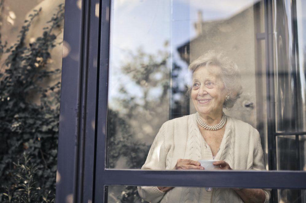femme aînée, sourire, hors fenêtre, tenue, thé