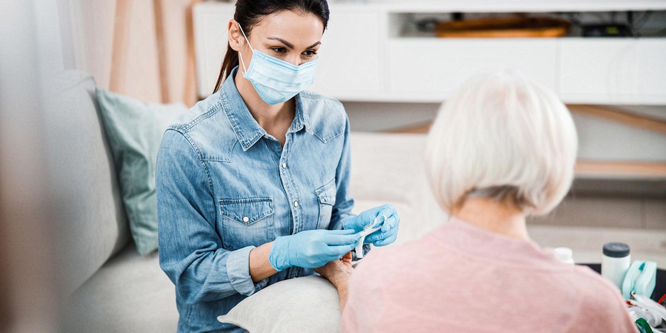 Femme au masque s'occupant d'un patient âgé