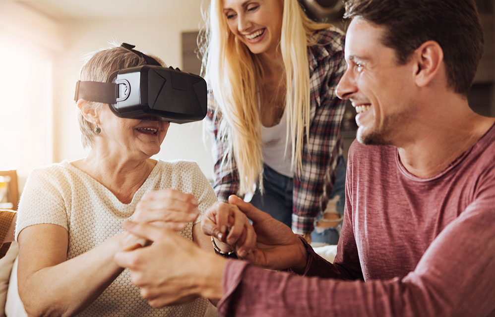 Senior woman and family using VR goggles
