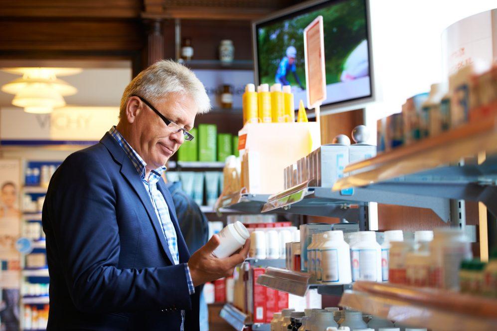 homme adulte regardant des médicaments en pharmacie