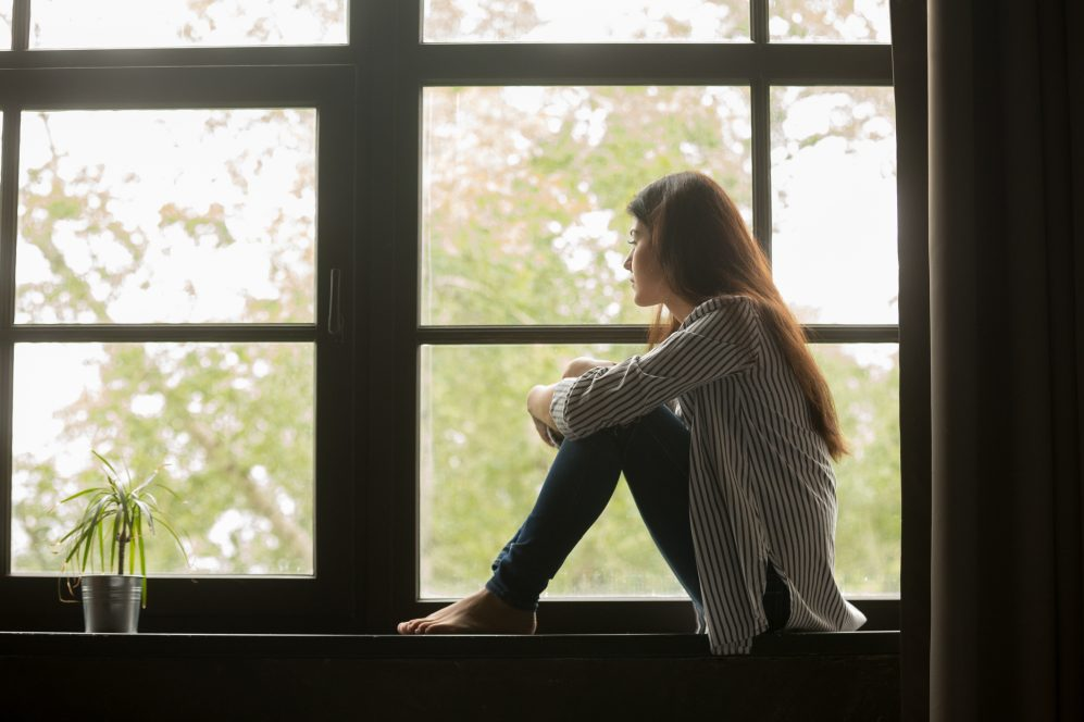 woman sitting on windowsill embracing knees and looking outside