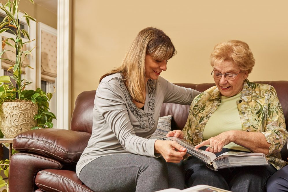 elderly mother and daughter looking through photo album