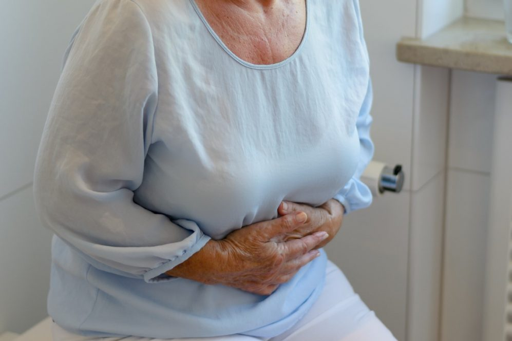 senior woman holding stomach in pain
